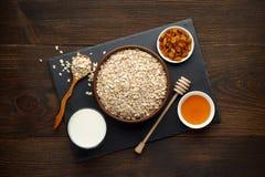 Desayuno sano en fondo de madera rústico La avena forma escamas con la leche, miel y las pasas en pizarra suben Fotos de archivo
