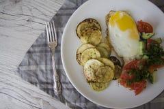 Desayuno sano: huevos fritos calientes y verduras cocidas imagenes de archivo