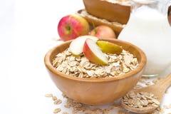 Desayuno sano - la avena forma escamas con las manzanas en un cuenco y una leche Imagen de archivo libre de regalías