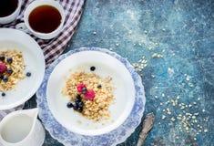 Desayuno sano: la harina de avena forma escamas con las bayas y el té/el café foto de archivo