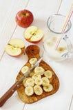 Desayuno sano: Preparación del smoothie del plátano de manzana Foto de archivo libre de regalías