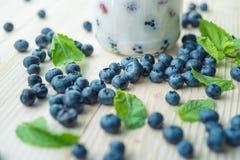 Desayuno sano rústico con el arándano y el yogur en un vidrio en una tabla de madera Vidrio de yogur hecho en casa con las bayas  Fotos de archivo libres de regalías
