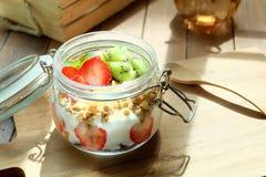 Desayuno sano y colorido por mañana caliente: Yogur con la fruta del granola, de la fresa y de kiwi Imagen de archivo libre de regalías