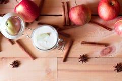 Desayuno sano: yogur con las manzanas y el canela en fondo de madera Imagenes de archivo