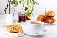 Desayuno - taza de café, de cruasanes, de atasco y de frutas en la tabla blanca imagenes de archivo