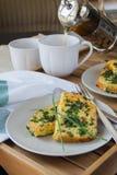 Desayuno: Tostada francesa en un par de placas, tazas de té blancas, luz natural Fotografía de archivo