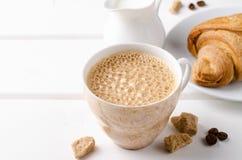 Desayuno tradicional con los cruasanes y el café frescos en el fondo de madera blanco Foto de archivo libre de regalías