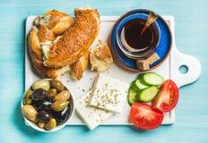 Desayuno tradicional turco con el queso feta, las verduras, las aceitunas, el panecillo del simit y el té Imagen de archivo libre de regalías