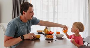 Desayuno tranquilo para el hijo del padre y del bebé almacen de metraje de vídeo