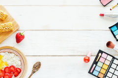 Desayuno y cosméticos femeninos en una tabla blanca Fotografía de archivo