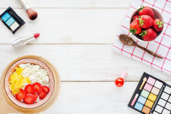 Desayuno y cosméticos femeninos en una tabla blanca Imagenes de archivo