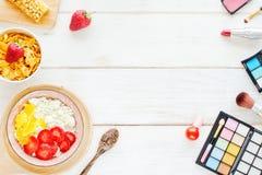 Desayuno y cosméticos femeninos en una tabla blanca Imagen de archivo libre de regalías