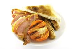 Desayuno y tostada en una placa blanca Fotografía de archivo libre de regalías