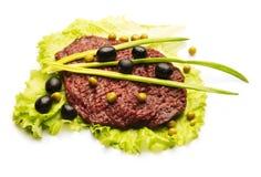 Desbaste a carne decorada com cebola, azeitona, e salada Fotografia de Stock Royalty Free