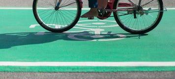 Descalzo completando un ciclo en carril verde de la trayectoria de la bici con el símbolo de Bikeway Imagenes de archivo