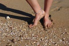 Descalzo en la playa - arena, c?scaras y dedos del pie desnudos imagenes de archivo