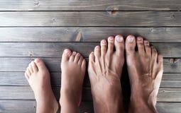 Descalzo, pies en piso de entarimado de madera, adulto y niño, familia Imagen de archivo