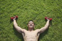 Descamisado, sonriendo, hombre muscular que miente en hierba con las pesas de gimnasia en Pekín, visión desde arriba Fotos de archivo