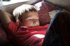 Descansando e lendo o adolescente que veste o t-shirt vermelho em retroiluminado foto de stock royalty free