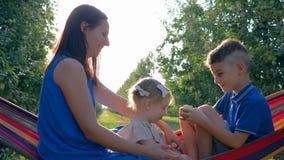 Descanse no jardim, mãe nova com as crianças jogadas na rede no pomar de fruto durante a colheita filme