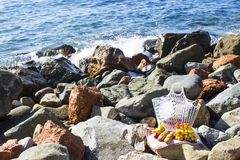 Descanse pelo mar com uvas, maçãs, peras, baguettes, vinho e uma cesta na coberta imagens de stock