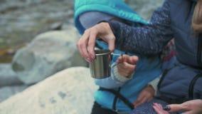 Descanse y beba la agua caliente cerca del río de la montaña viajes de la familia Ambiente de la gente por las montañas, ríos, co almacen de video