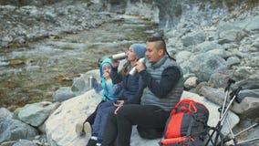 Descanse y beba la agua caliente cerca del río de la montaña viajes de la familia Ambiente de la gente por las montañas, ríos, co almacen de metraje de vídeo