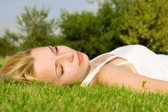 Descanso da mulher na grama verde Imagens de Stock
