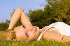 Descanso da mulher na grama verde do verão Fotografia de Stock Royalty Free