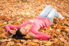 Descanso da mulher nova no parque do outono fotografia de stock