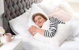 Descanso do abraço da jovem mulher ao dormir na cama fotografia de stock royalty free