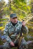 Descanso do caçador, sentando-se em um log Fotografia de Stock Royalty Free