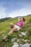 Descanso do caminhante da mulher, encontrando-se altamente na montanha Imagem de Stock