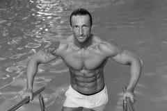 Descanso do homem relaxado na borda da piscina imagens de stock royalty free