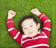 Descanso e mão de sorriso pequenos do menino acima no prado Imagem de Stock Royalty Free