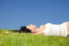 Descanso feliz da mulher na grama verde fotografia de stock royalty free