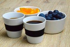 Descanso para tomar café con los arándanos frescos y las rebanadas anaranjadas fotos de archivo libres de regalías
