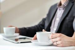 ¡Descanso para tomar café corporativo! Empresarios jovenes que se sientan en el tabl Fotos de archivo