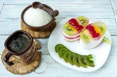 Descanso para tomar café de la porción Pastel de queso con las rebanadas de la fruta y el kiwi cortado fotografía de archivo