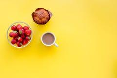 Descanso para tomar café dulce en oficina Café, fresa, magdalena en copyspace amarillo de la opinión superior del fondo Fotografía de archivo