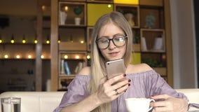 Descanso para tomar café Mujer que usa smartphone y la sonrisa metrajes