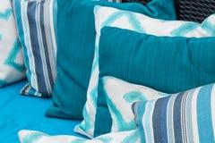 Descansos coloridos em um sofá azul Branco, azul, obscuridade - azul imagens de stock royalty free