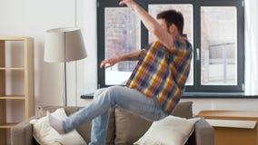 Descansos deixando cair do homem e salto ao sofá em casa filme