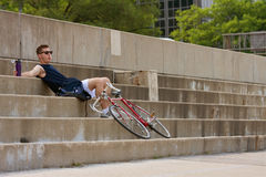 Descansos do homem da bicicleta da equitação na cidade Fotografia de Stock