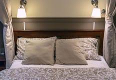 Descansos em uma cama em um quarto do clássico-estilo Interior de um quarto clássico em tons bege foto de stock royalty free