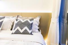 Descansos modelados na cama com a cortina branca no quarto Imagem de Stock Royalty Free