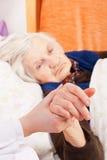 Descansos sós idosos da mulher na cama Fotos de Stock
