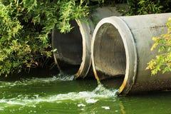 Descarga da água de esgoto em um rio fotografia de stock royalty free