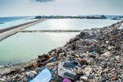 Descarga de basura cerca de la playa del océano por completo del humo, de la litera, de botellas plásticas, de desperdicios y de  foto de archivo libre de regalías