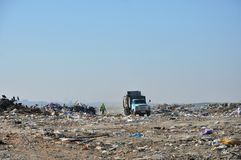Descarga de basura de la ciudad y el camión de basura viejo foto de archivo